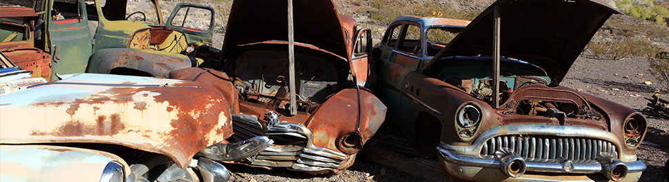 Image of old rusty cars sitting in the dirt of a salvage yard